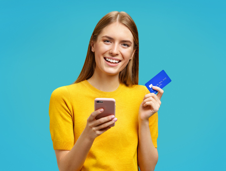 Smiling girl holds smartphone and credit card. Photo of beautiful girl in yellow sweater on blue background. Emotions and pleasant feelings concept. 写真素材