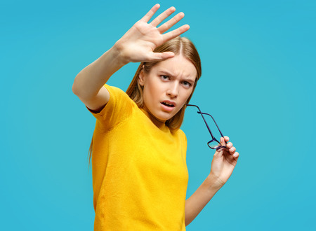 Scared girl outstretched her palm, hiding her face. Photo of attractive girl in yellow sweater on blue background. Emotions and feelings concept. Banque d'images - 121015035