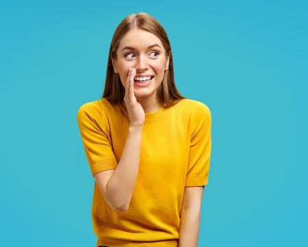 Niña sonriente comparte sus secretos con alguien. Foto de chica atractiva en suéter amarillo sobre fondo azul.
