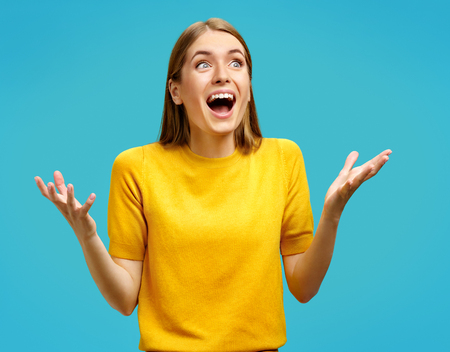 Happy girl gestures actively from happiness. Photo of attractive girl in yellow sweater on blue background. Emotions and pleasant feelings concept.