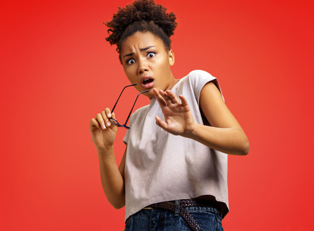Scared girl outstretched her palm, hiding her face. Photo of african american girl wears casual outfit on red background. Emotions and pleasant feelings concept.