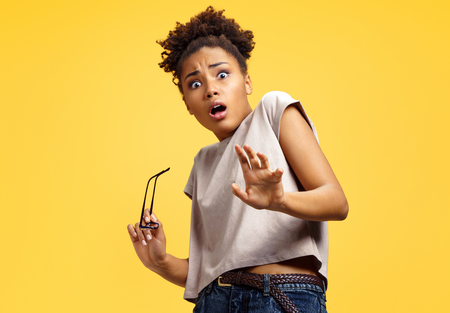 Scared girl outstretched her palm, hiding her face. Photo of african american girl wears casual outfit on yellow background. Emotions and pleasant feelings concept.