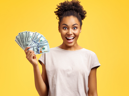 Happy girl holds cash money. Photo of african american girl wears casual outfit on yellow background. Emotions and pleasant feelings concept. 写真素材