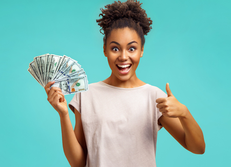 Young girl shows money and like gesture. Photo of african american girl wears casual outfit on turquoise background. Emotions and pleasant feelings concept.
