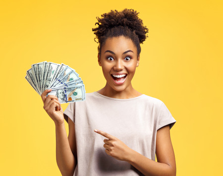 Young girl points her forefinger to the money. Photo of african american girl wears casual outfit on yellow background. Emotions and pleasant feelings concept.