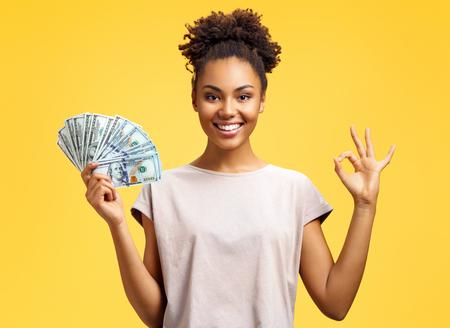 Niña sonriente muestra dinero en efectivo y excelente señal, demuestra que todo está bien. Foto de niña afroamericana viste ropa casual sobre fondo amarillo. Concepto de emociones y sentimientos agradables.