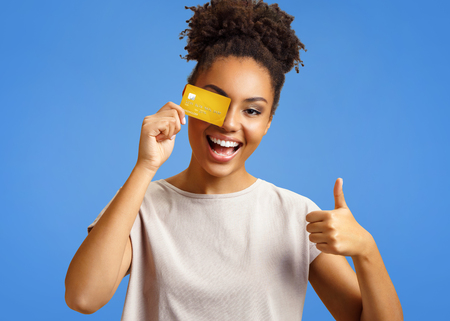 Happy girl holds credit card and shows thumb up. Photo of african american girl wears casual outfit on blue background. Emotions and pleasant feelings concept. Stock Photo