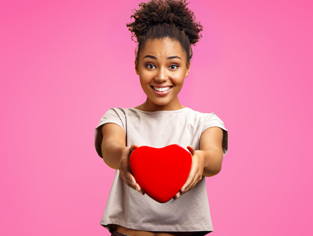 Lovely young girl holds heart shaped gift box. Photo of african american girl wears casual outfit on pink background. Emotions and pleasant feelings concept.