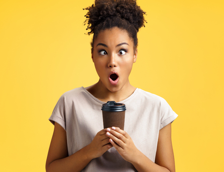 Crazy girl holds cup of hot coffee. Photo of african american girl wears casual outfit on yellow background. Emotions and pleasant feelings concept.