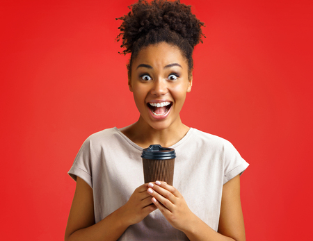 Joyful girl holds cup of hot coffee. Photo of african american girl wears casual outfit on red background. Emotions and pleasant feelings concept.