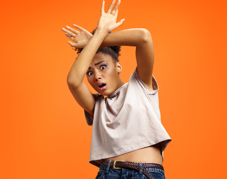Scared girl outstretched her palms, hiding her face. Photo of african american girl wears casual outfit on orange background. Emotions and feelings concept. 写真素材