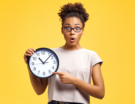 Time to work! Student with shocked face holds clock and points to them. Photo of african american girl wears casual outfit on yellow background. Emotions and pleasant feelings concept. Stock Photo