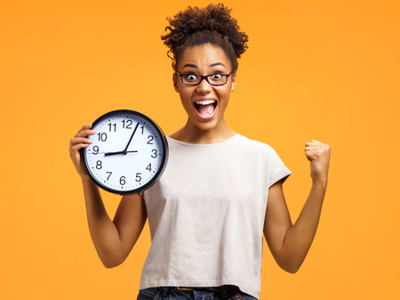 Joyful girl holds clock, raises fist and shouts loudly. Photo of african american girl wears casual outfit on orange background. Emotions and pleasant feelings concept.