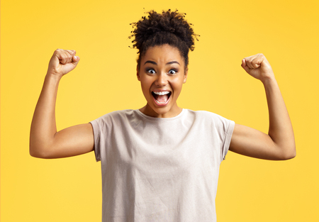 Lucky girl winner clenches fists. Photo of african american girl wears casual outfit on yellow background. Emotions and pleasant feelings concept.