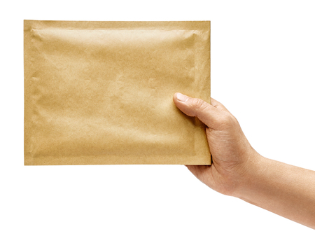 Mans hand holds a yellow envelope isolated on white background. Close up. High resolution product