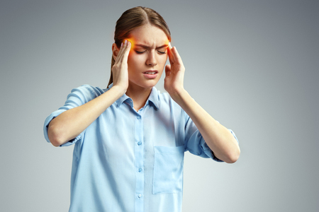 Woman with pain in her temples. Photo of american woman in blue shirt suffering from stress or headache grimacing in pain on gray background. Medical concept Stock Photo - 123035178