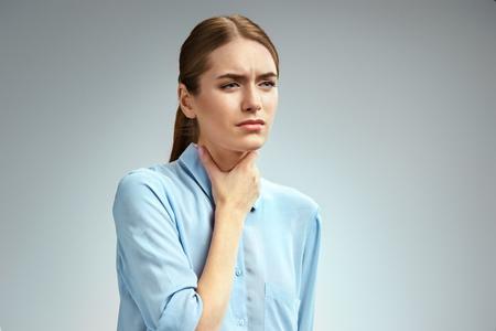Halsschmerzen. Frau, die ihre entzündete Kehle hält Foto der amerikanischen Frau im blauen Hemd auf grauem Hintergrund. Medizinisches Konzept Standard-Bild