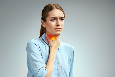 Throat pain. Woman holding her inflamed throat. Photo of american woman in blue shirt on gray background. Medical concept