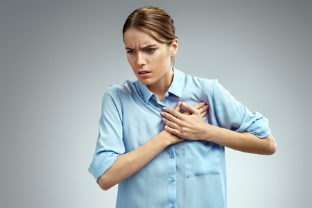 Woman holds hands on painful chest. Photo of american woman in blue shirt on gray background. Medical concept. Heart attack