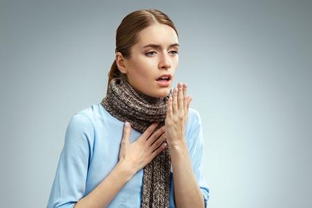 Femme malade avec mal de gorge. Photo d'une femme américaine en chemise bleue souffrant du virus de la grippe sur fond gris. Notion médicale Banque d'images