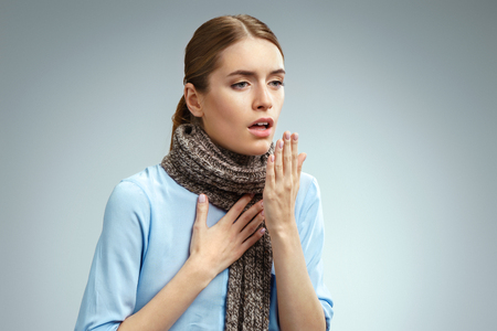 Sick woman with sore throat. Photo of american woman in blue shirt suffering virus of flu on gray background. Medical concept