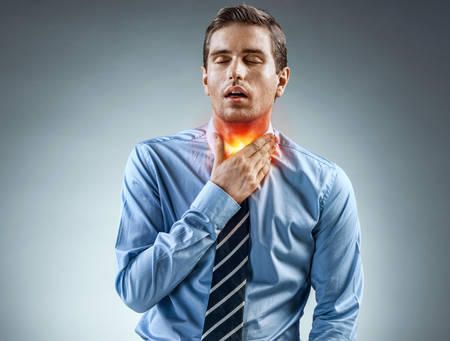Throat Pain. Office worker holding his inflamed throat. Photo of man in blue shirt and tie on gray background. Medical concept