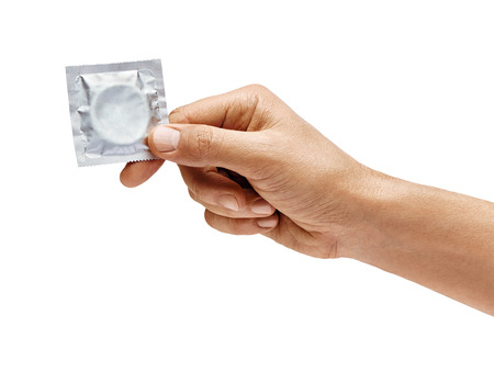Mans hand with condom isolated on white background. High resolution product. Close up Stock Photo
