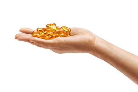 Many capsules Omega 3 in mans hand isolated on white background. Close up. High resolution product. Health care concept