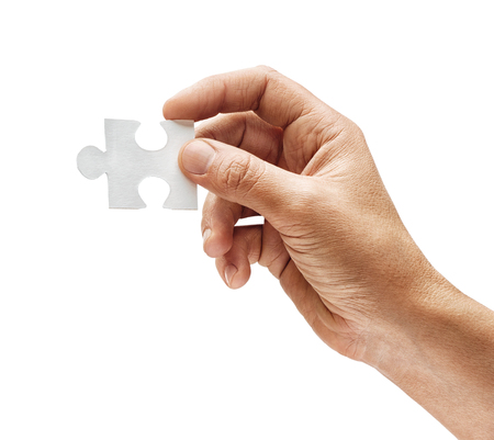 Mans hand holding one puzzle element isolated on white background. Close up. High resolution product