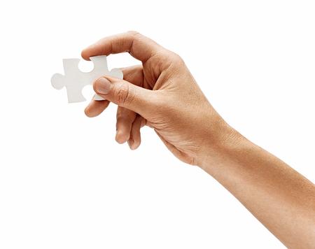 La main de l'homme avec un élément de puzzle isolé sur fond blanc. Fermer. Produit haute résolution