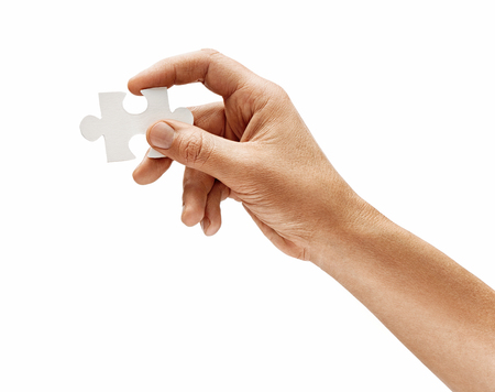Mans hand with one puzzle element isolated on white background. Close up. High resolution product 写真素材