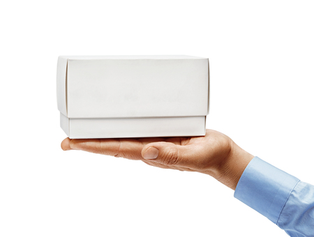 Mans hand in a shirt holds white box isolated on white background. Close up. High resolution 写真素材