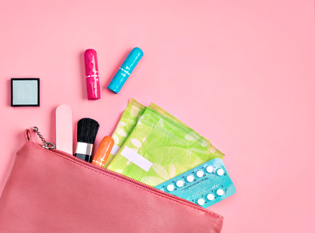 Ladys bag. Sanitary pads and tampons in cosmetic bag on pink background. Concept of critical days, menstruation Reklamní fotografie