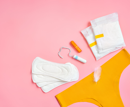 Yellow pants with sanitary napkins and tampons on pink background. Concept of critical days, menstruation