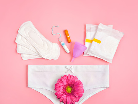 White pants with sanitary napkins, tampons, menstrual cup, flower on pink background. Concept of critical days, menstruation Reklamní fotografie