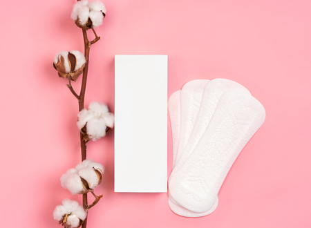 White packaging of sanitary pads with cotton flowers on pink background. Concept of critical days, menstruation