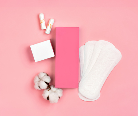 Packaging of sanitary pads and packaging of tampons with cotton flowers on pink background. Concept of critical days, menstruation Reklamní fotografie