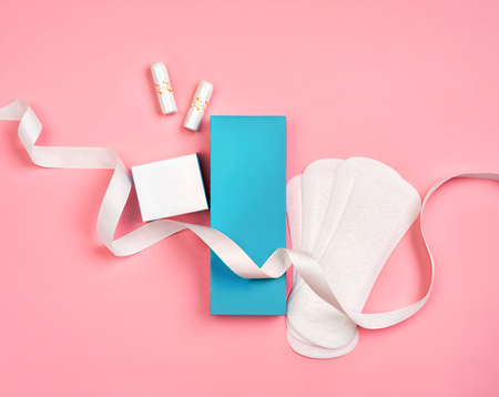 Packaging of sanitary pads and packaging of tampons on pink background. Concept of critical days, menstruation
