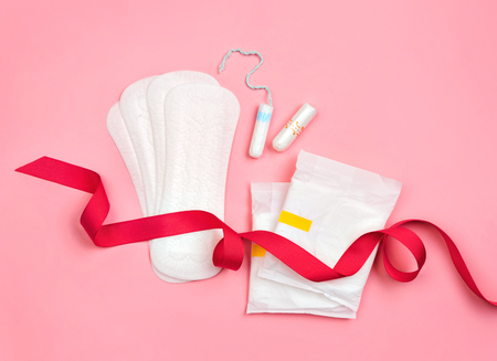 Sanitary and daily napkins, tampons with red ribbon on pink background. Concept of critical days, menstruation