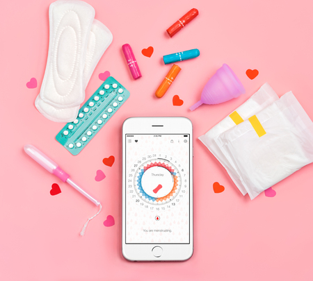 Phone with menstrual calendar. Sanitary napkins, tampons, contraceptive pills and menstrual cup on pink background. Concept of critical days, menstruation