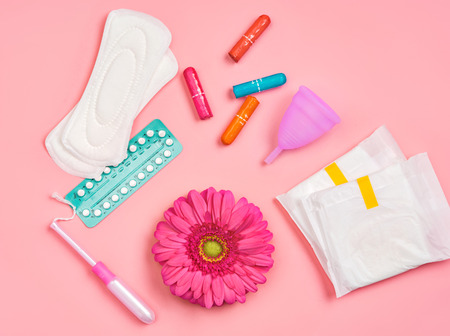 Sanitary napkins, tampons, contraceptive pills, menstrual cup and gerbera flower on pink background. Concept of critical days, menstruation Reklamní fotografie
