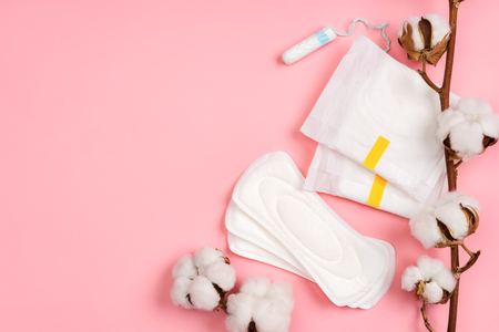 Menstrual napkins and tampons with cotton flowers on pink background. Concept of critical days, menstruation