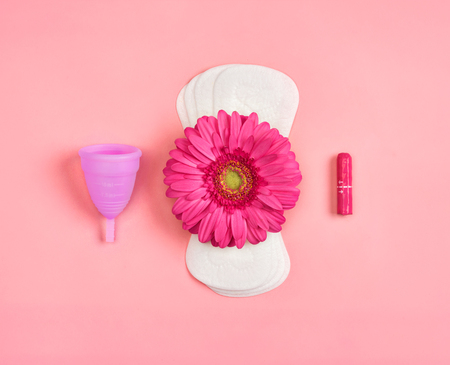 Daily sanitary napkins, tampon and menstrual cup on pink background. Concept of critical days, menstruation Reklamní fotografie