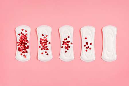 Menstrual pads with red glitters on pink background. Concept of critical days, menstruation