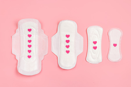 Set of different sanitary napkins with hearts on pink background. Concept of critical days, menstruation