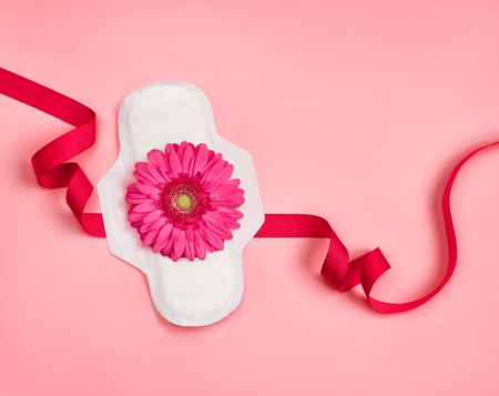 Sanitary napkin with gerbera flower on pink background. Concept of critical days, menstruation 写真素材