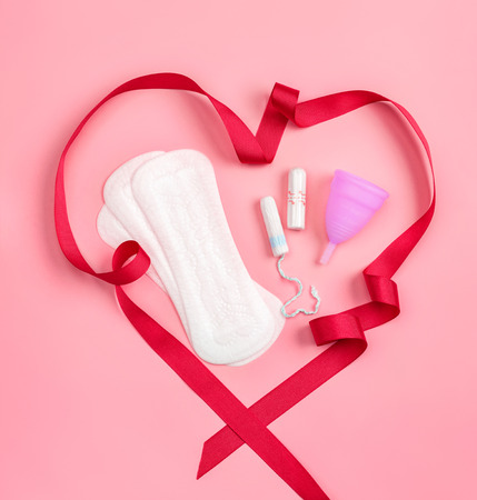 Daily sanitary napkins, tampon and menstrual cup with red ribbon on pink background. Concept of critical days, menstruation