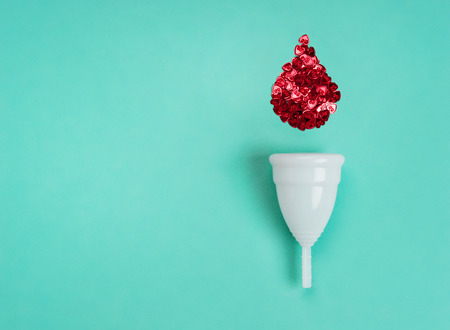 White menstrual cup with red drop of blood on turquoise background. Concept of critical days, menstruation 写真素材 - 123827753