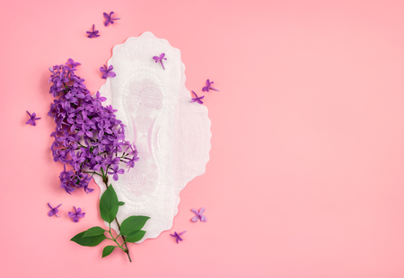 Sanitary napkin with lilac flower on pink background. Concept of critical days, menstruation 写真素材