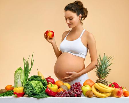 La donna incinta con frutta e verdura sul tavolo, tiene la mela su sfondo beige. Concetto di gravidanza, maternità, preparazione e aspettativa
